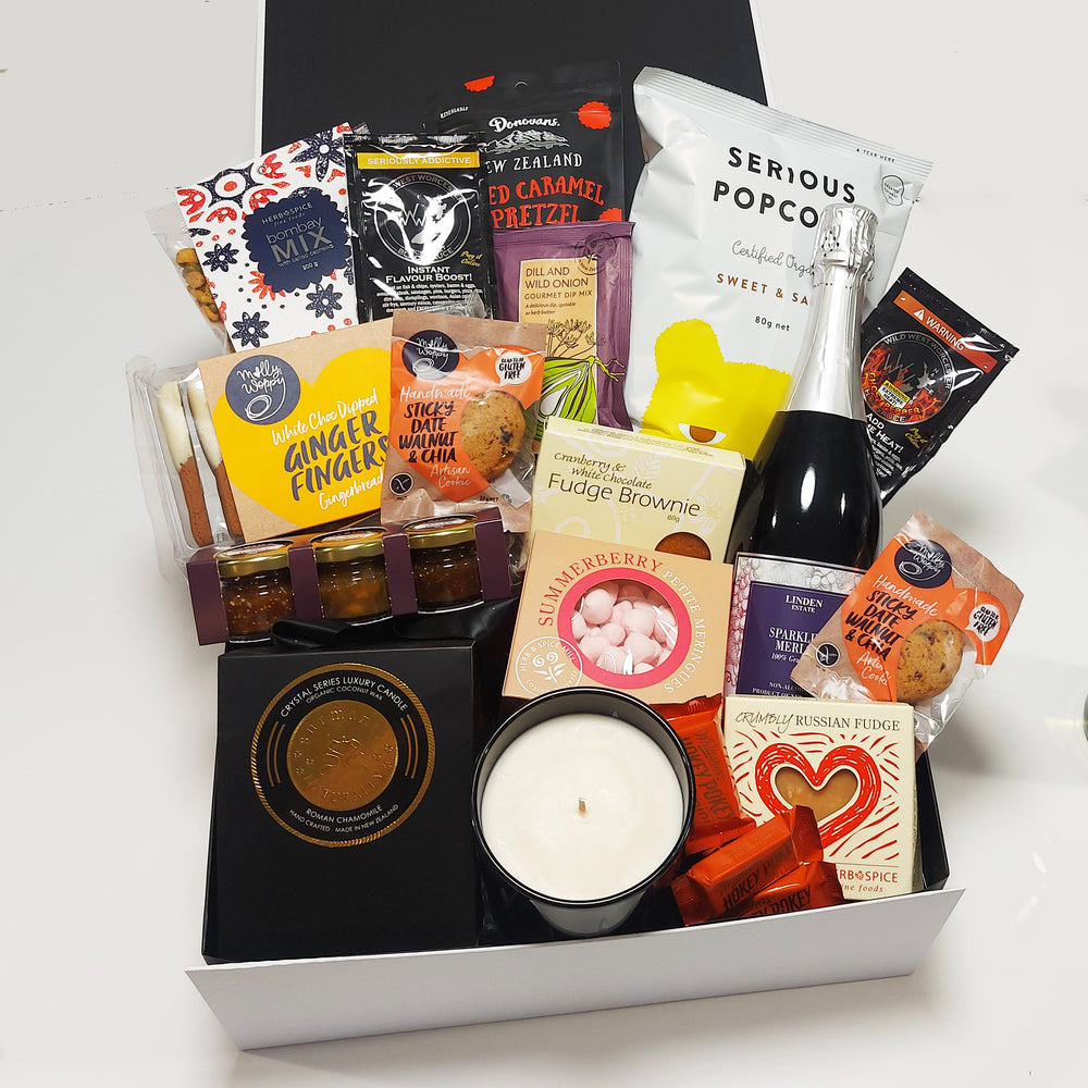 House warming gift basket with large candle grape juice, chocolate, gingerbread & more presented in a modern gift box.
