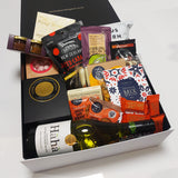 House warming gift basket with large candle, wine, chocolate, gingerbread & more presented in a modern gift box.