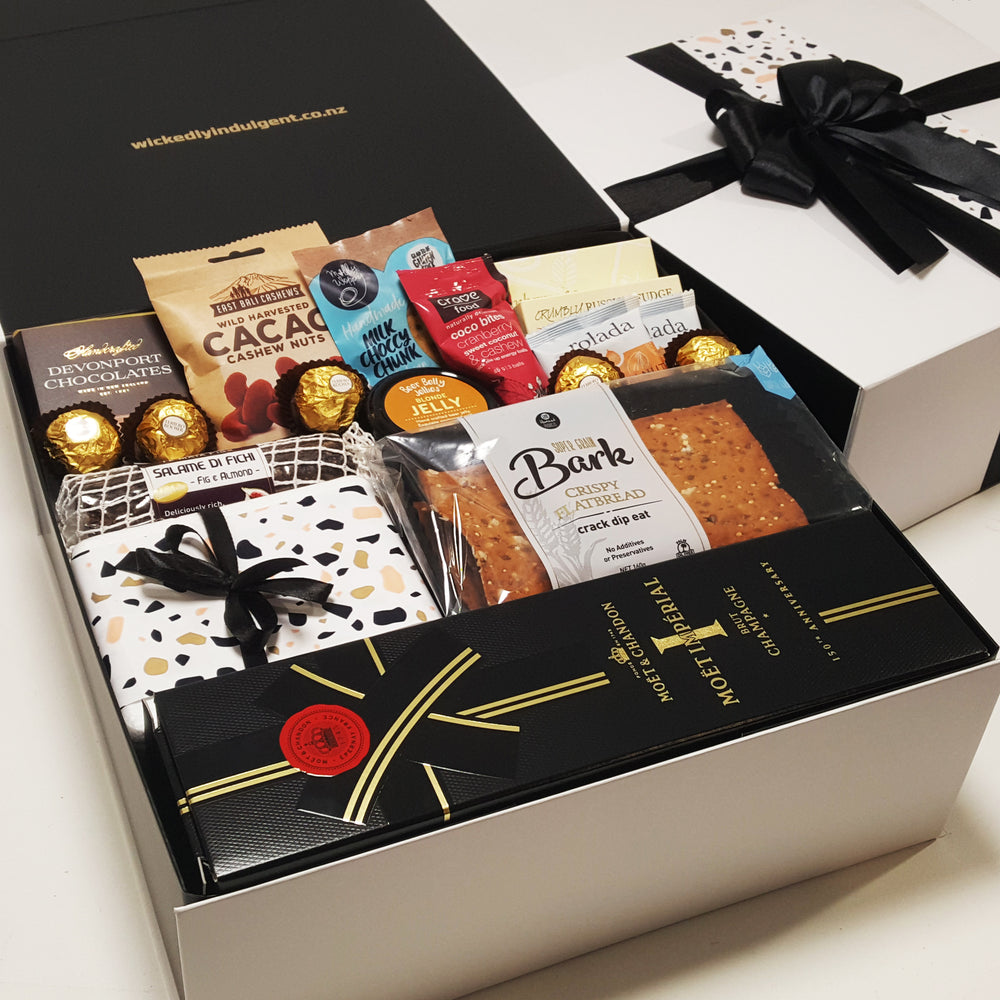 Lets pop bottles gift basket with Moet, cheese, chocolate, cashews & more presented in a modern gift box.