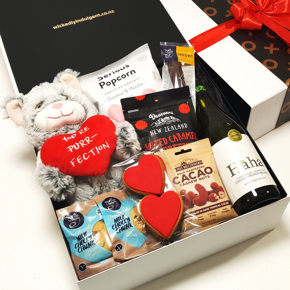 Romantic gift basket with a love soft toy, wine and delicious gourmet nibbles, presented in a modern gift box.