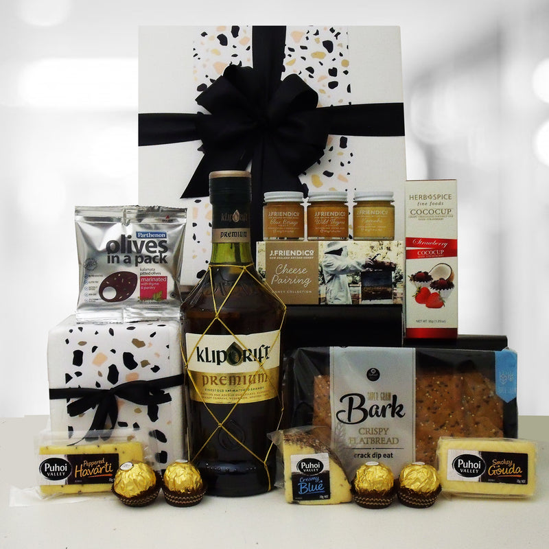 Brandy gift box with honey paired with cheese and olives.