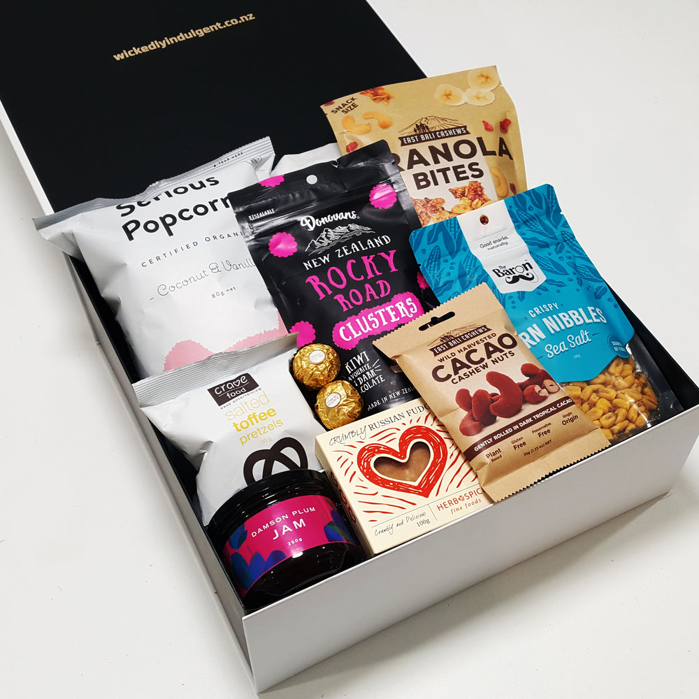 Sweet tooth gift hamper with plum jam, popcorn, granola bites, russian fudge, chocolates and more, all presented in a modern gift box.
