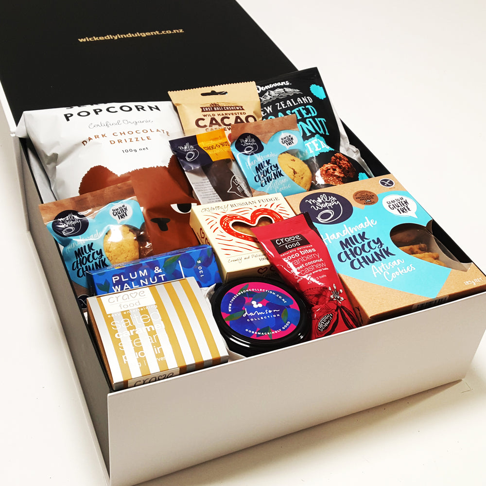 Sweet treat gift hamper with plum jam, shortbread, steam pudding, chocolate and more presented in a modern gift box.