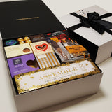 Celebration stash gift basket with champagne, chocolate, shortbread, plum paste and more presented in a modern gift box.