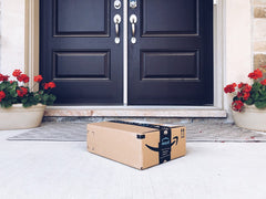 Amazon Prime cardboard box on a front porch. The front porch is concrete with flower pots and blue double front doors.