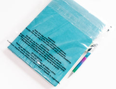 Blue notebook in a clear poly mailer with a suffocation warning printed on the bag