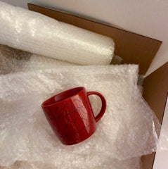 Cardboard box with bubble wrap and a red coffee mug