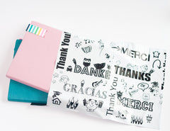 White poly mailer with thank you printed in black in several languages.  Pink and teal notebooks are visible coming out of the top of the mailer.