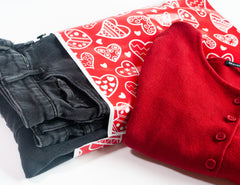 Red poly mailer with white hearts. A pair of black jeans are in the mailer with a red shirt to the side.