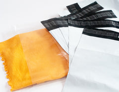 Several white poly mailers fanned out on a white background with a yellow scarf