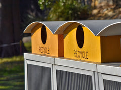 Yellow and metal recycling bins in an outdoor park