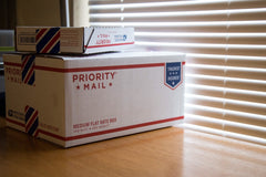 Two Priority Mail cardboard boxes sitting on a table by a window