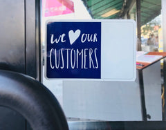 We love our customers sign on a wooden business door window