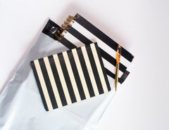 White poly mailer with a black and white striped journal inside. A smaller striped journal sits on top of the mailer.