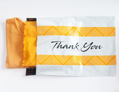 White poly mailer with thank you printed in black.  Yellow bars surround the word thank you.