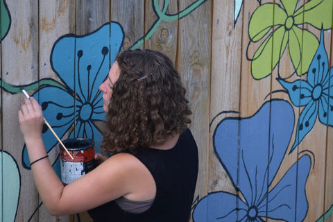Eryn working on a fence mural