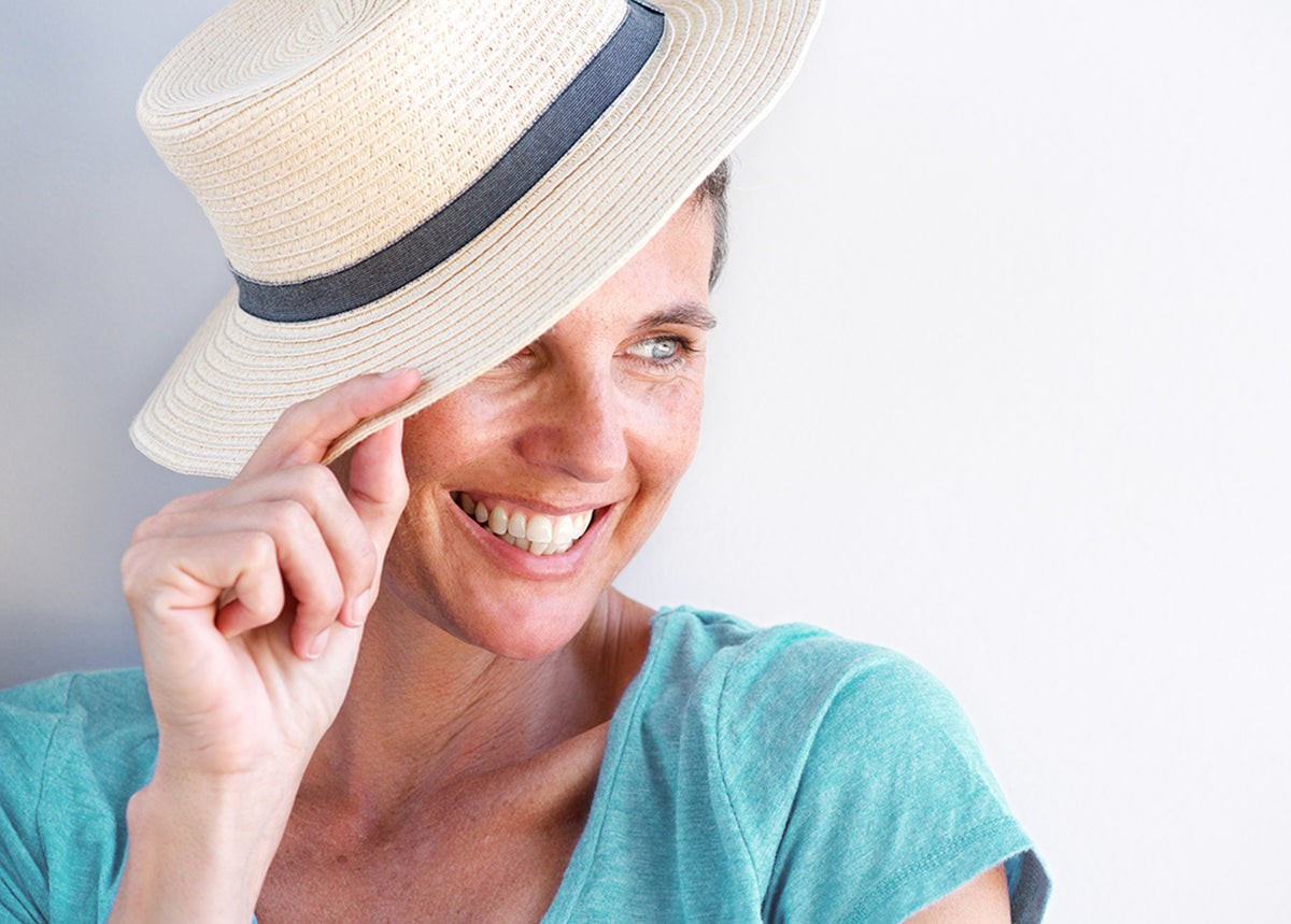 Menopausal woman smiling and relaxed leaning against a wall with a straw hat on