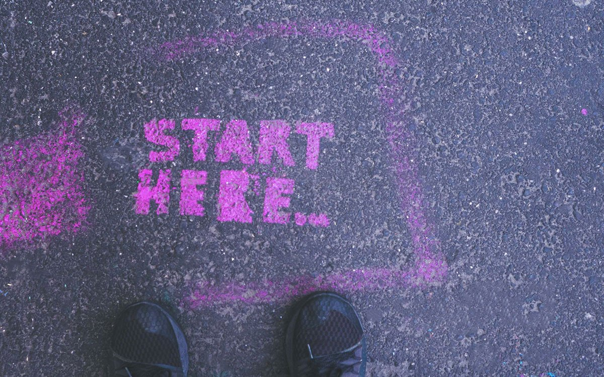Start here stencil spray painted in pink on a asphalt footpath