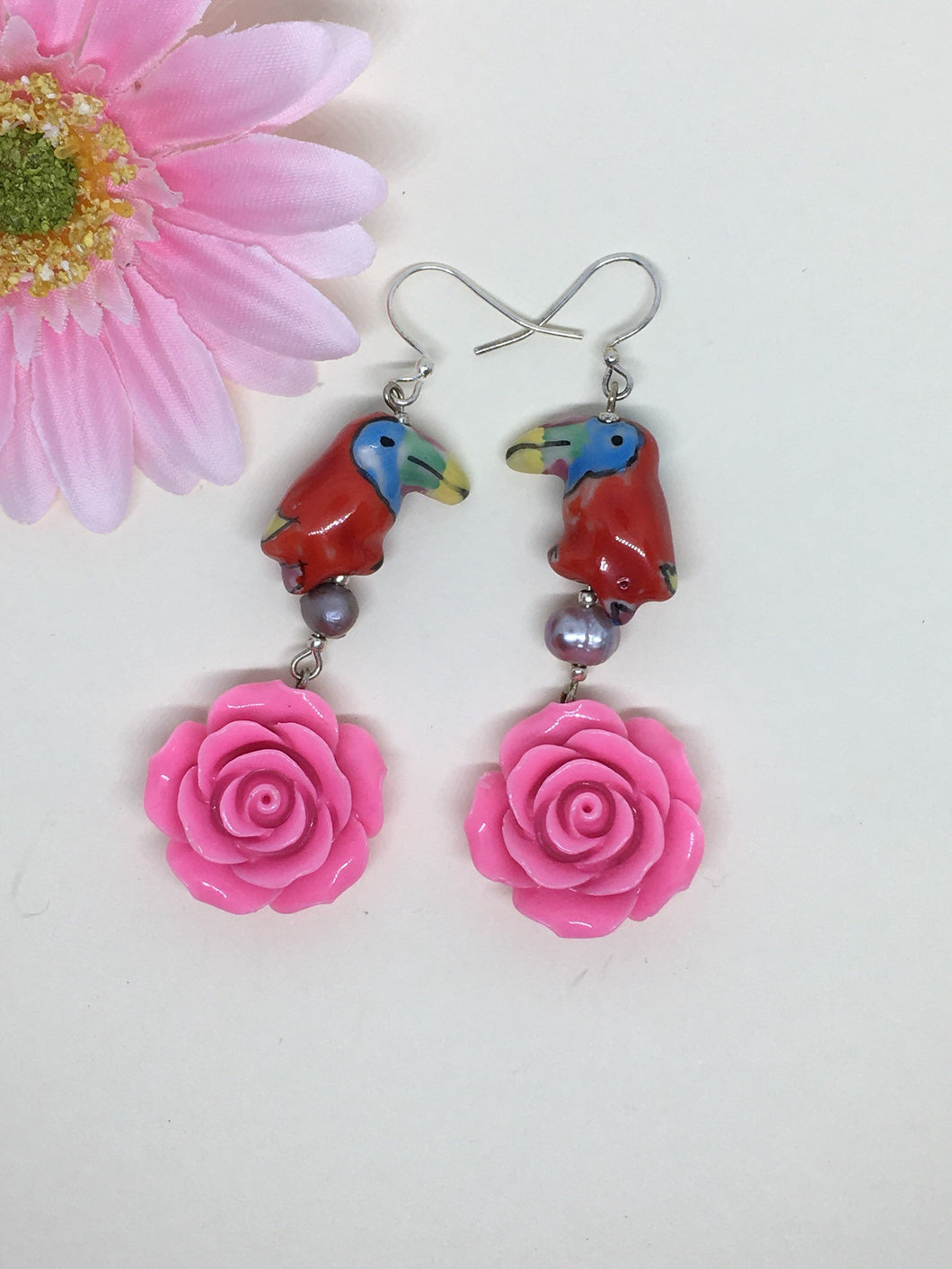 Red Rose earring - Ceramic Parrot on Freshwater Pearl above pink Rose earring.