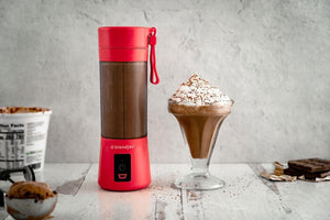 Red BlendJet on a counter next to a chocolate shake and surrounded by chocolate and cocoa powder