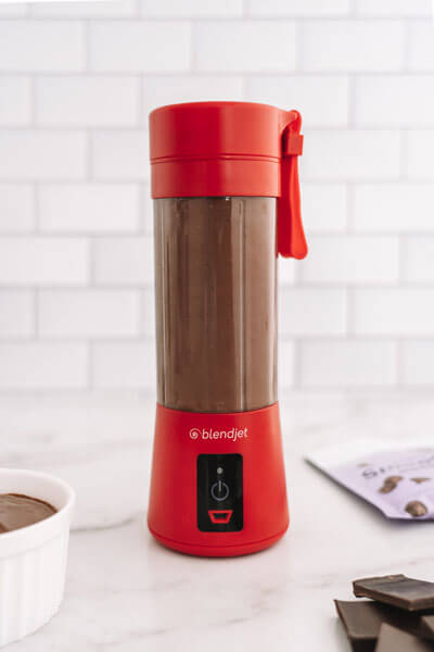 Red BlendJet on a counter with chocolate and a JetPack of smoothie mix