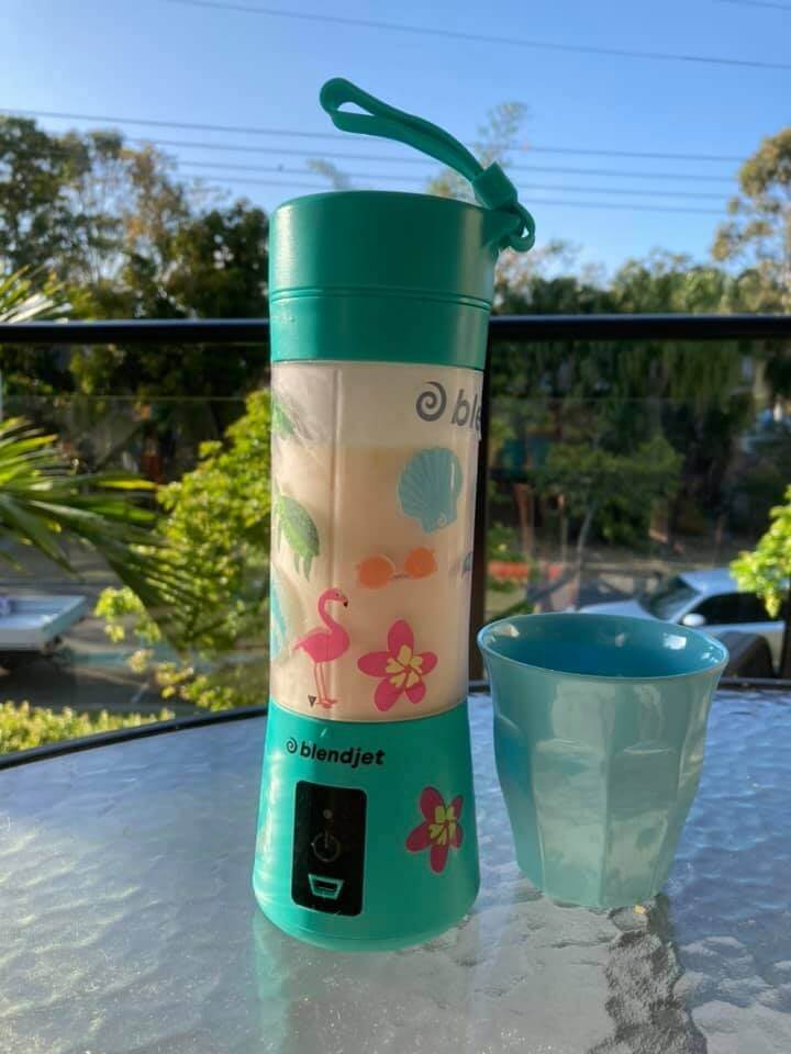teal blendjet portable blender with stickers on it and glass on patio table