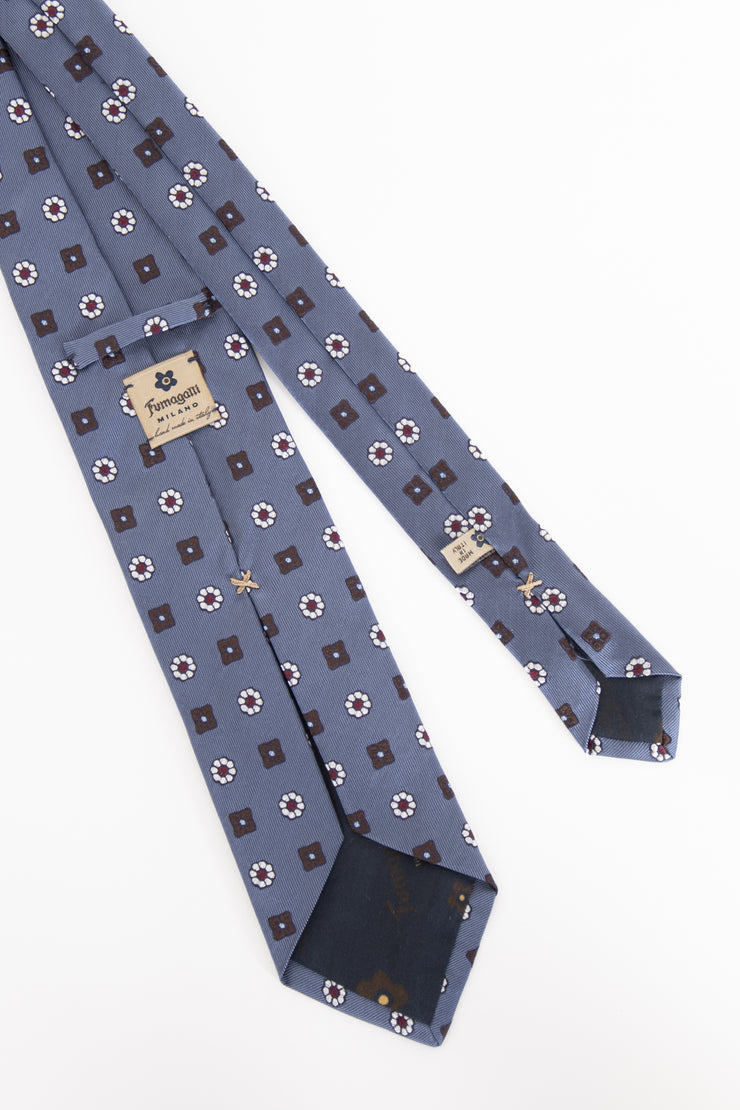 dettaglio del cartellino fumagalli su una cravatta in seta azzurro-tag fumagalli detail on a light blue silk tie