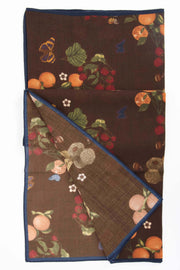 green leaves, tangerines, raspberries and white flowers on a brown wool scarf