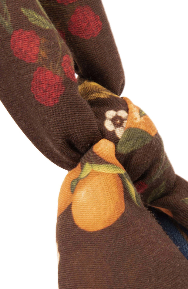 tangerines, raspberries and white flower on the scarf