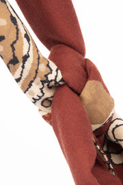 the detail of a knot on a red and light brown scarf