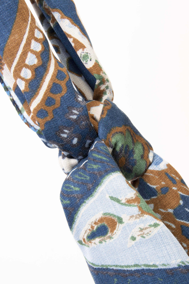 the pattern of this scarf is full of brown and light blue flower and leaves