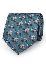 floral patterned tie with white flowers and green leaves on a turquoise background