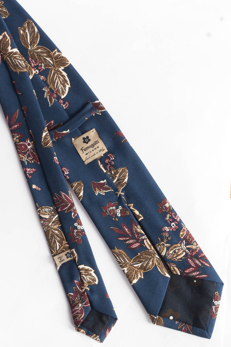 back of the tie printed with red and brown leaves on a blue backgrounf