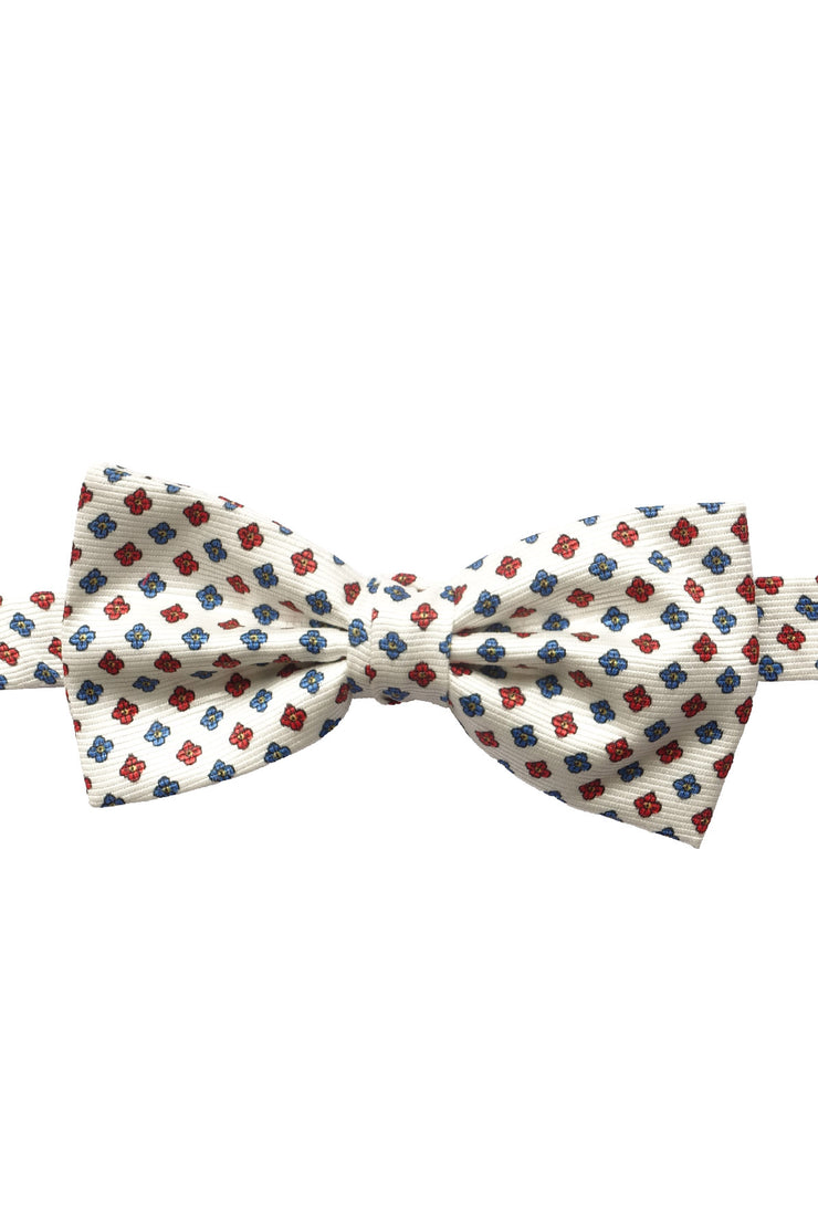 blue and red flowers stand out on a white background on this silk printed hand made ready-tied bow tie