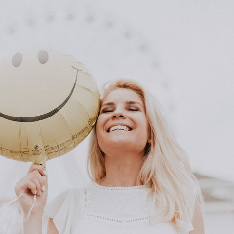 women with blonde hair and happy yellow smiley ballon at a carnival