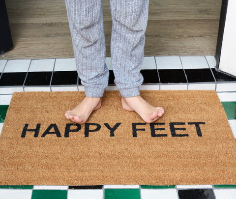 "feet on coir doormat that states ""happy feet"""