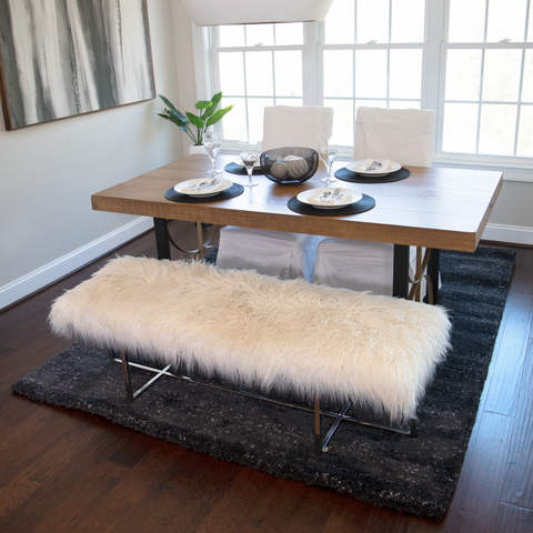 a wooden modern table with two white chairs in the background. One long faux fur ivory colored bench in the foreground. There is a blag shag rug with white speckles under the table and a modern black and white picture on the wall.