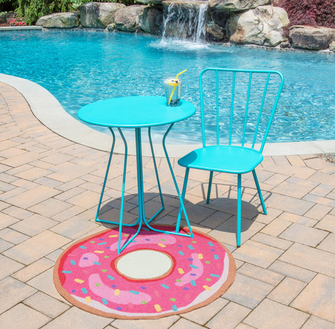 donut rug beside pool under turquoise outdoor table.