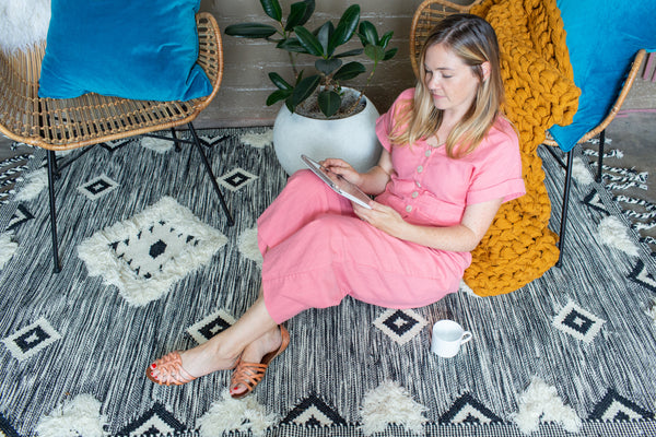 a woman in a pink romper leans against a rattan chair. There is a potted rubber plant to her right, and a mustard colored blanket behind her on the floor. She is wearing a pink jumpsuit and leather sandals. There is a black and white rug with diamonds underneath her.