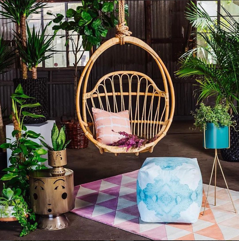 hanging rattan swing above pink triangle rug. Boho room with palms.