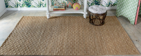natural jute area rug infront of a palm tree wall papered wall.