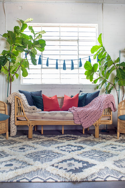 A rattan day bed sits under a large industrial window. It has two blankets draped on either side. There are orange and blue pillows agains the back. In the foreground is a black and white moroccan style rug. There are two large fig trees on either side of the bed.