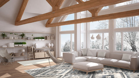 Open floor plan with grey modern sofa and large windows. A grey and blue diamond pattern rug is on the floor under the furniture setting. There are large wooden beams on the vaulted ceiling and the outdoor vista is snowy.