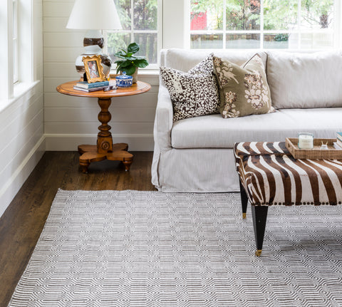 an elegant living room with a brown zebra ottomon on top of a brown and white geometric area rug.