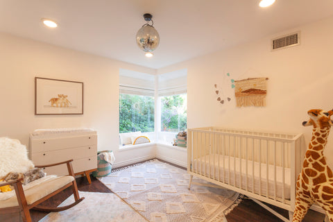 nursery with disco ball hanging from ceiling. a white crib is in the right of the shot with a stuffed giraffe in the corner. two area rugs are layered on the floor. There is a big window in the corner and a rocking chair on the left.
