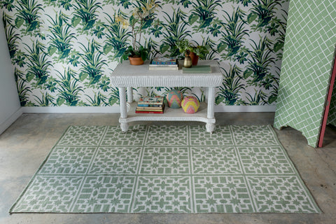 green and white area rug infront of a palm tree wall papered wall.