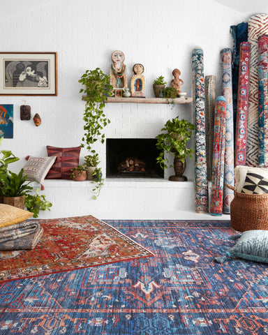 two rugs at an angle on the floor infront of a white brick modern fireplace.