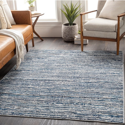 light blue and grey solid rug under a brown leather couch and white chair.