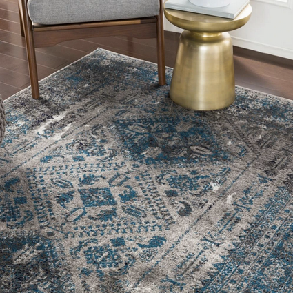blue and grey tribal rug close up with gold side tabel and chair feet.