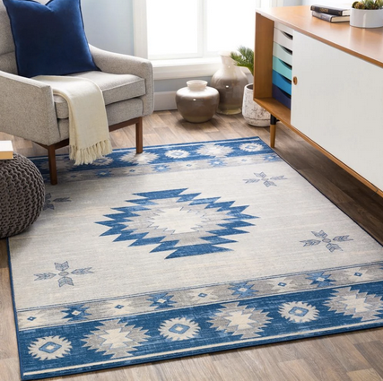 blue and ivory native american printed rug on the floor next to a white chair and white buffet table.